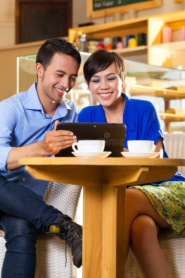 Mulher e homem asiáticos em uma cafetaria foto de stock