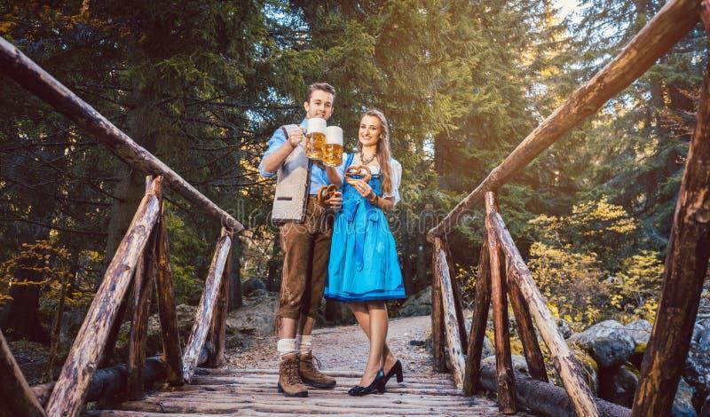 Mulher e homem com a cerveja que está na ponte em Baviera imagem de stock royalty free