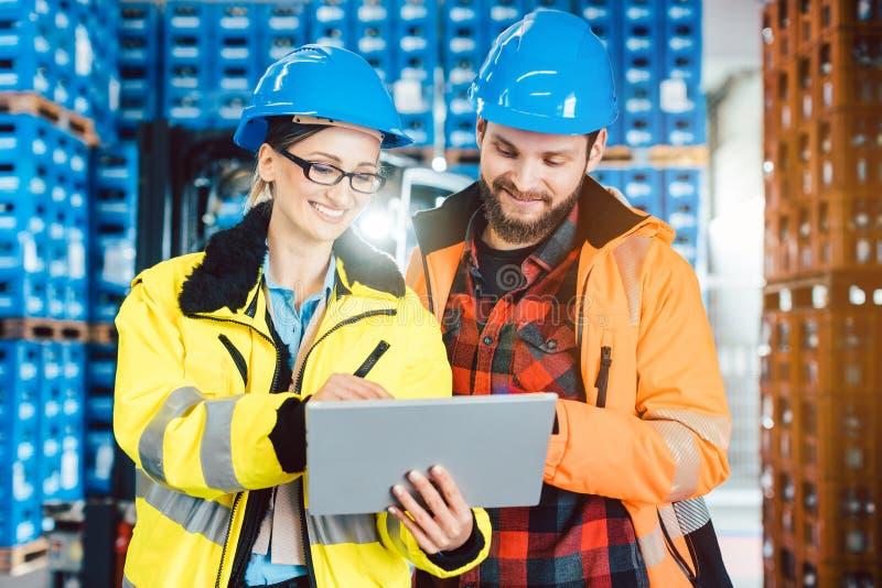 Mulher e homem como trabalhadores no centro da logística usando o computador foto de stock