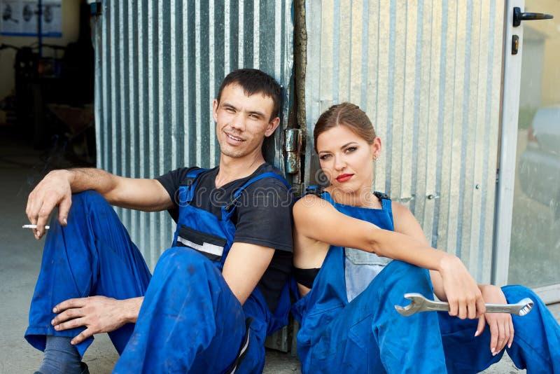 Mulher e homem dos mecânicos que sentam-se perto da garagem do reparo imagem de stock