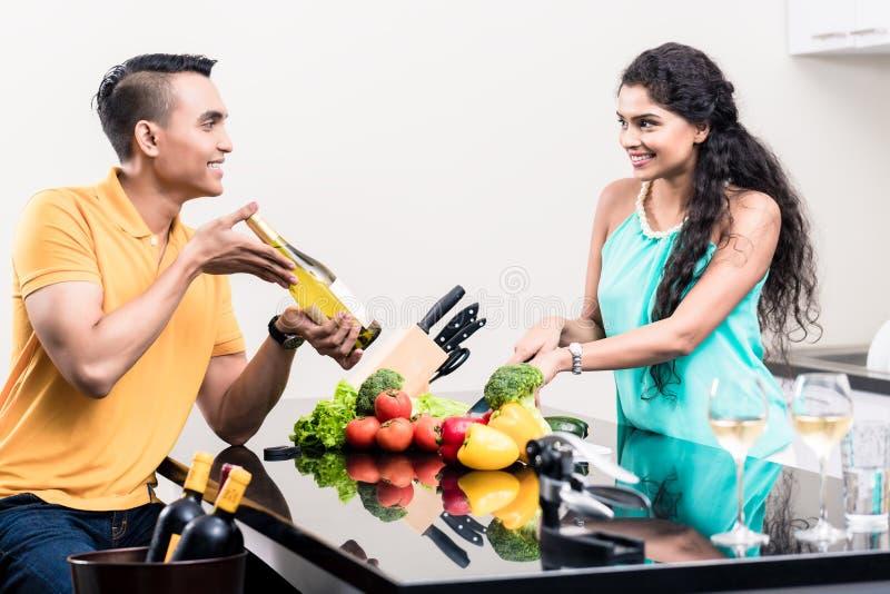 Mulher e homem indianos na cozinha com vinho tinto foto de stock