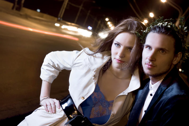 Mulher e homem na rua iluminada na noite fotografia de stock royalty free