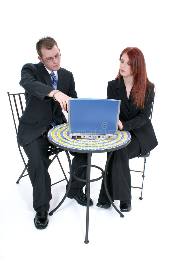 Mulher e homem novos bonitos de negócio na tabela com portátil