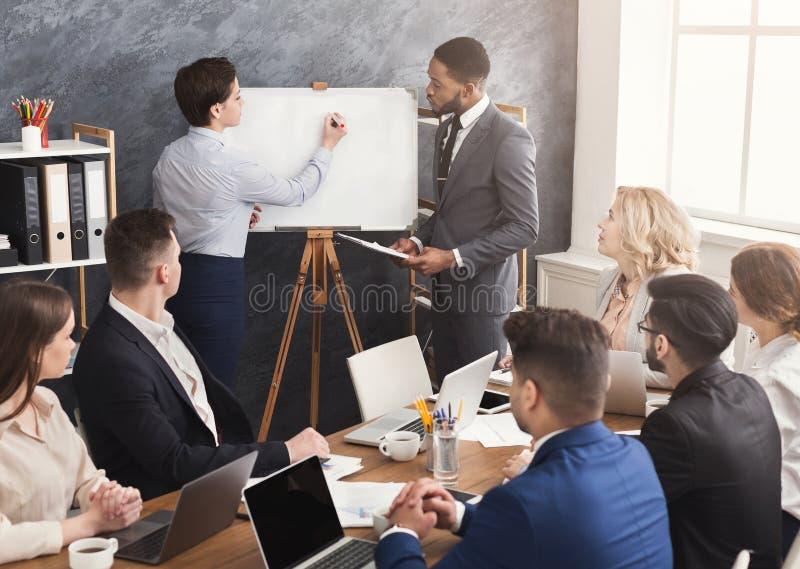 Mulher e homem que dão a apresentação aos colegas no escritório imagem de stock