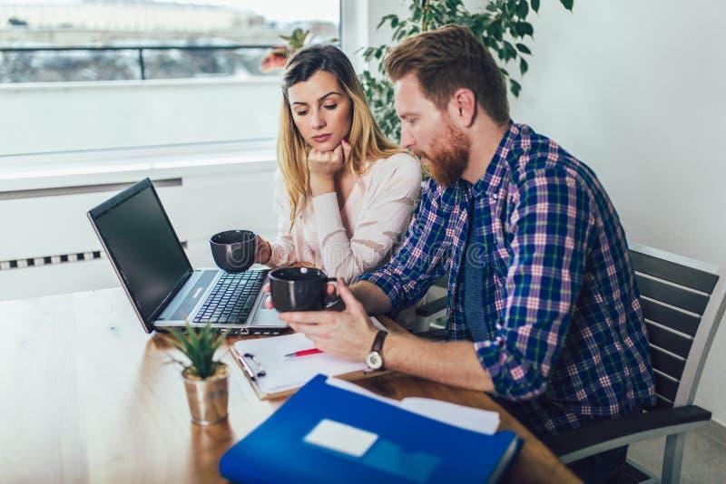Mulher e homem que fazem o documento junto, relatam o imposto em linha fotografia de stock