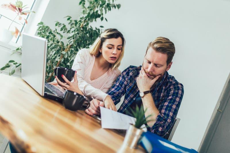 Mulher e homem que fazem o documento junto, relatam o imposto em linha imagens de stock royalty free