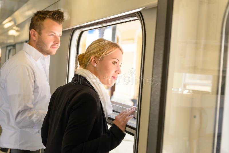 Mulher e homem que olham para fora o indicador do trem imagem de stock royalty free