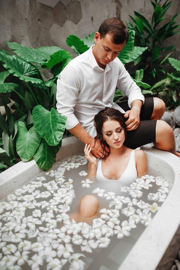 Mulher e homem que relaxam no banho com as flores tropicais exteriores no recurso do hotel de luxo imagem de stock