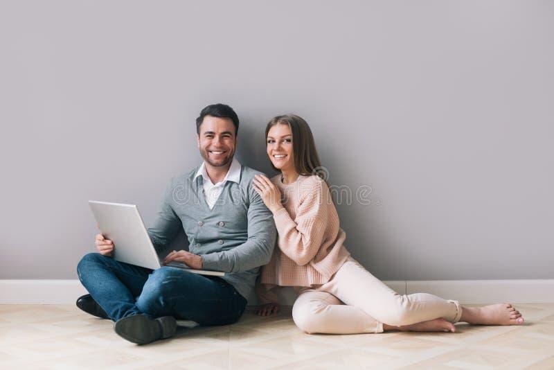 Mulher e homem que usa o portátil que senta-se no assoalho imagem de stock
