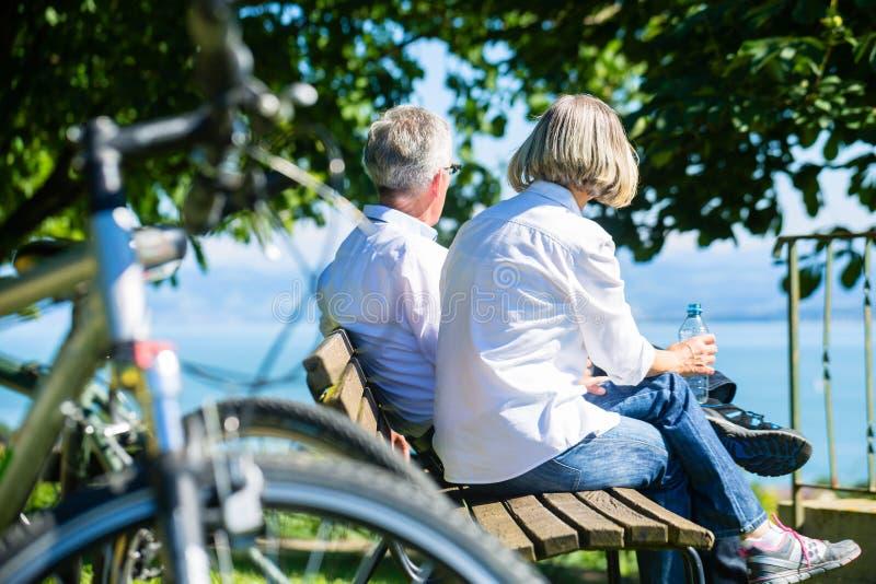 Mulher e homem superiores em repouso na viagem da bicicleta imagem de stock