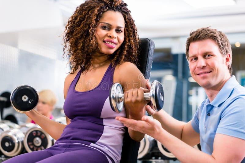 Mulher e instrutor africanos no exercício no gym fotos de stock