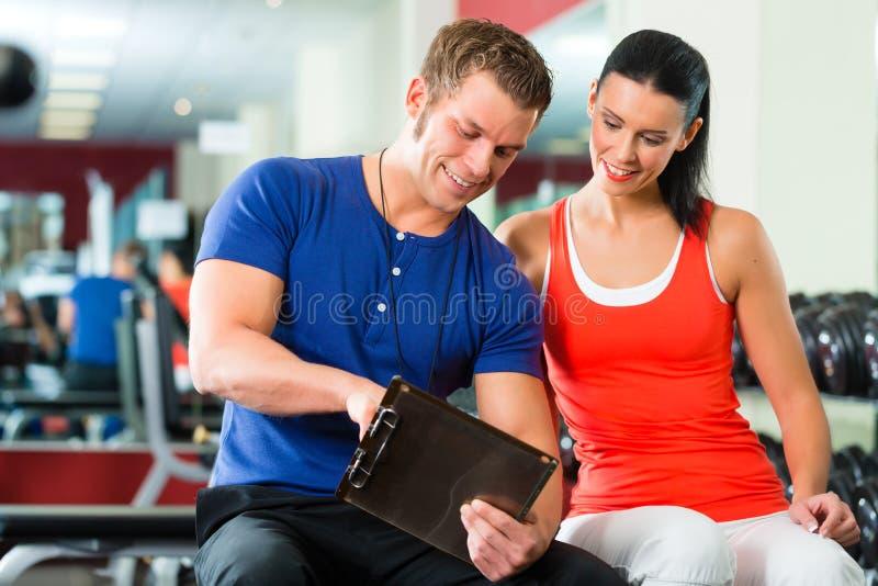 Mulher e instrutor pessoal no gym, com dumbbells imagem de stock royalty free