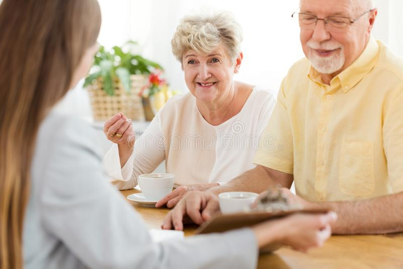 Mulher e marido superiores de sorriso que falam a um conselheiro financeiro imagens de stock