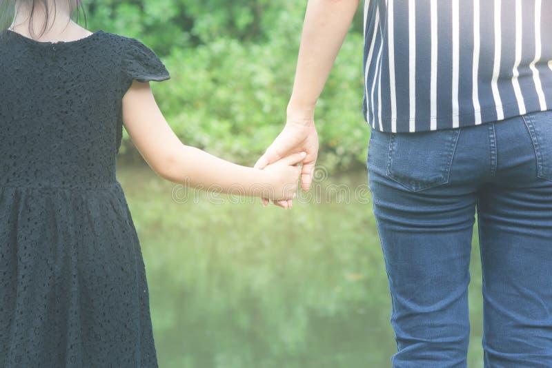 Mulher e menina bonito que mantêm as mãos unidas e que estão na grama verde no parque público nas horas de verão fotografia de stock