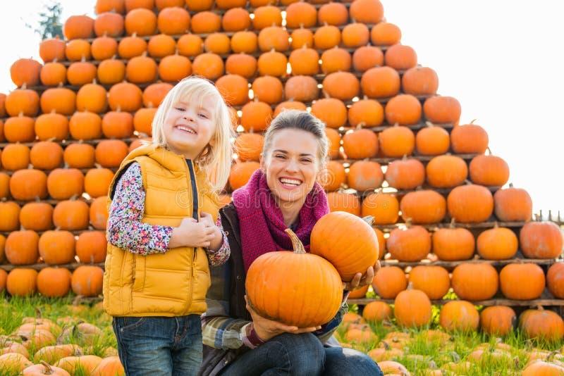 Mulher e menina de sorriso que guardam abóboras no outono fora foto de stock
