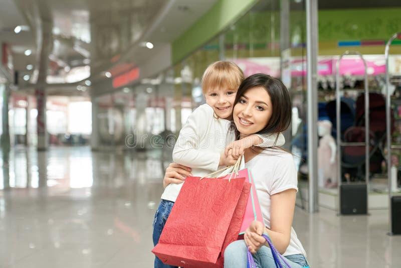 Mulher e menina felizes no levantamento, sorrindo no shopping imagens de stock
