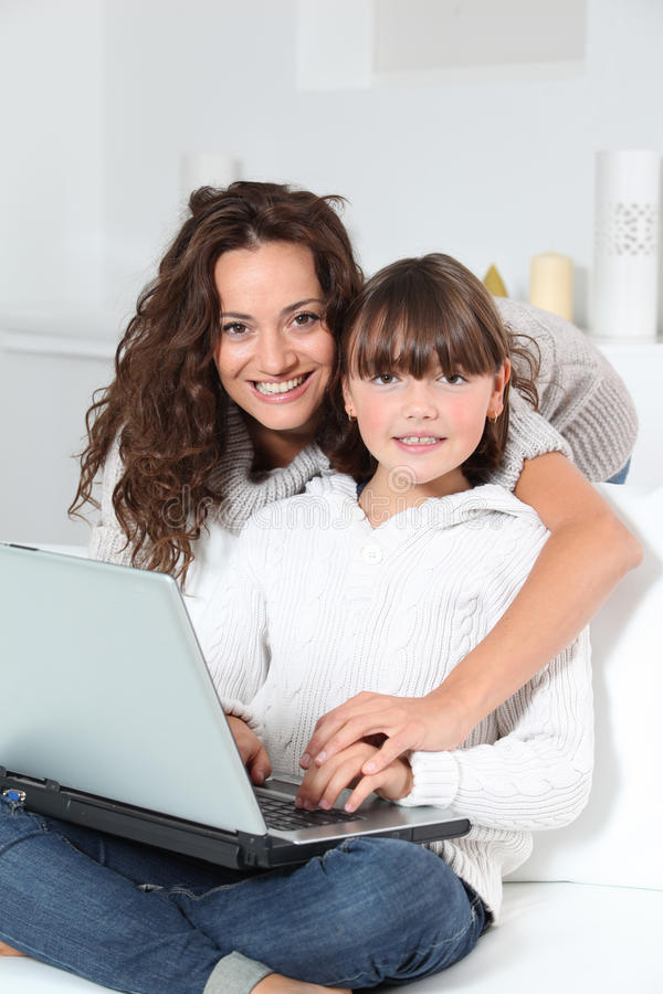 Mulher e menina na frente do computador imagens de stock
