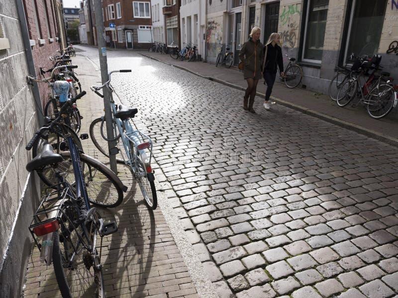 A mulher e a menina passam muitas bicicletas estacionadas no centro da cidade holandesa velha groningen imagem de stock