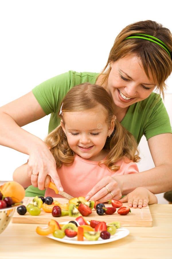Mulher e menina que preparam a salada de fruta imagens de stock