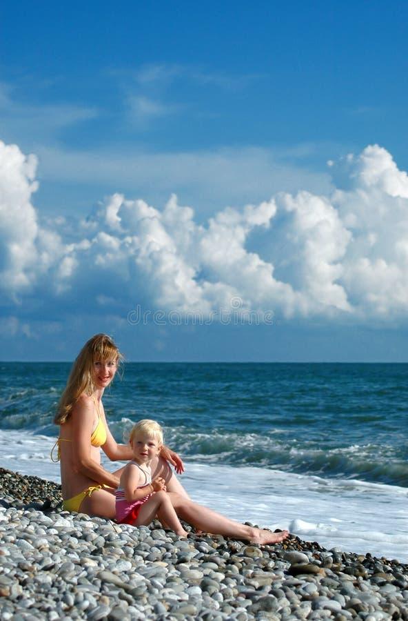 A mulher e a menina sentam-se no seacoast fotografia de stock