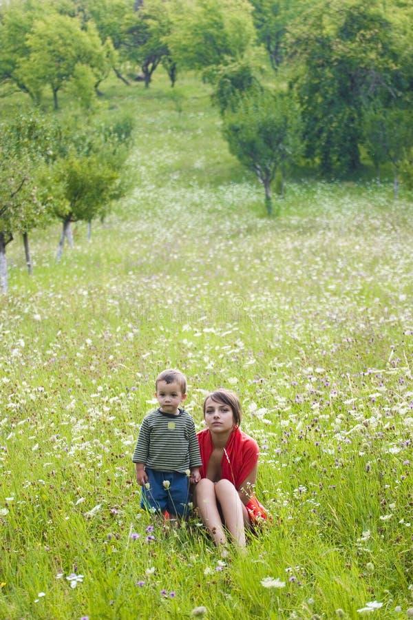 Mulher e menino no prado imagens de stock