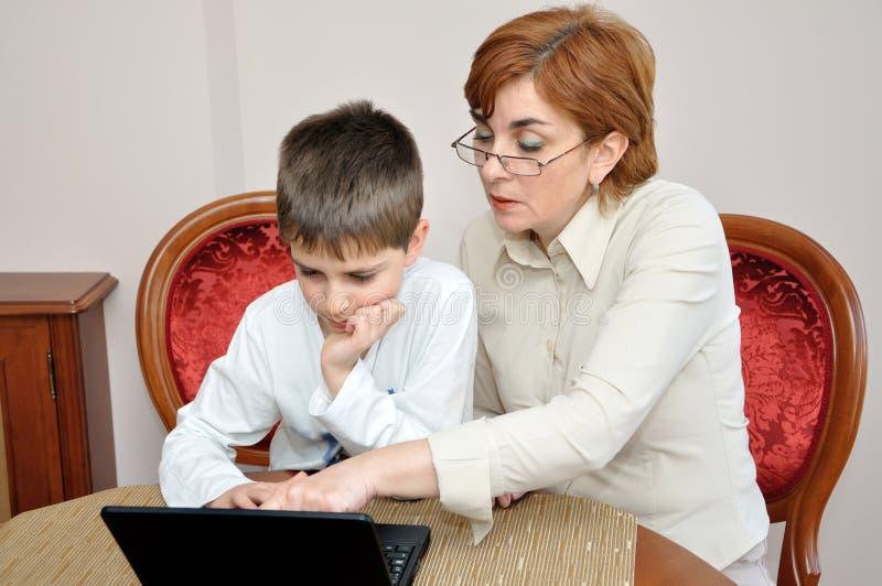 Mulher e menino novo com portátil imagens de stock