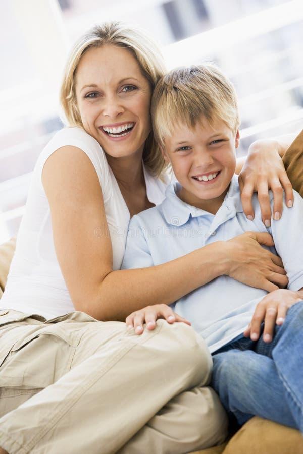 Mulher e menino novo que sentam-se no sorriso da sala de visitas fotografia de stock