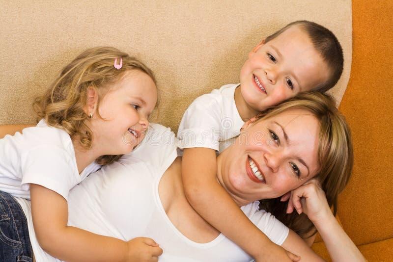 Mulher e miúdos no sofá fotos de stock