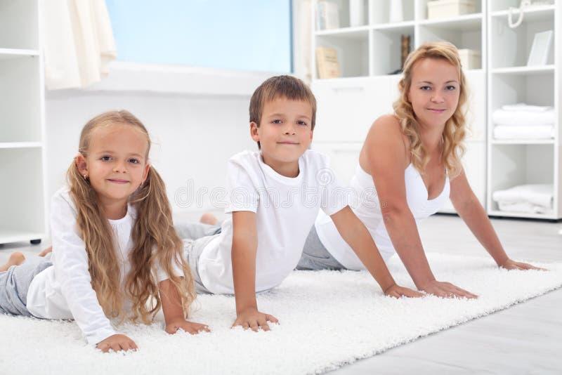Mulher e miúdos que esticam suas partes traseiras imagem de stock