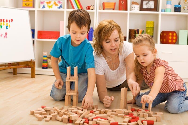 Mulher e miúdos que jogam com blocos de madeira