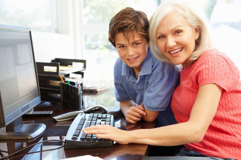 Mulher e neto meados de da idade que usa o computador fotografia de stock