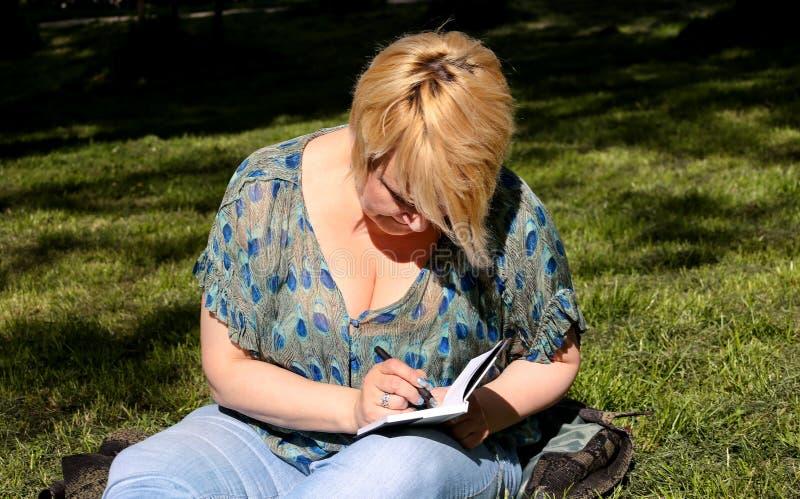 A mulher e o estudante que sentam-se na grama, tomam notas no caderno, aprendendo e escrevem pensamentos, escrevem o livro imagem de stock