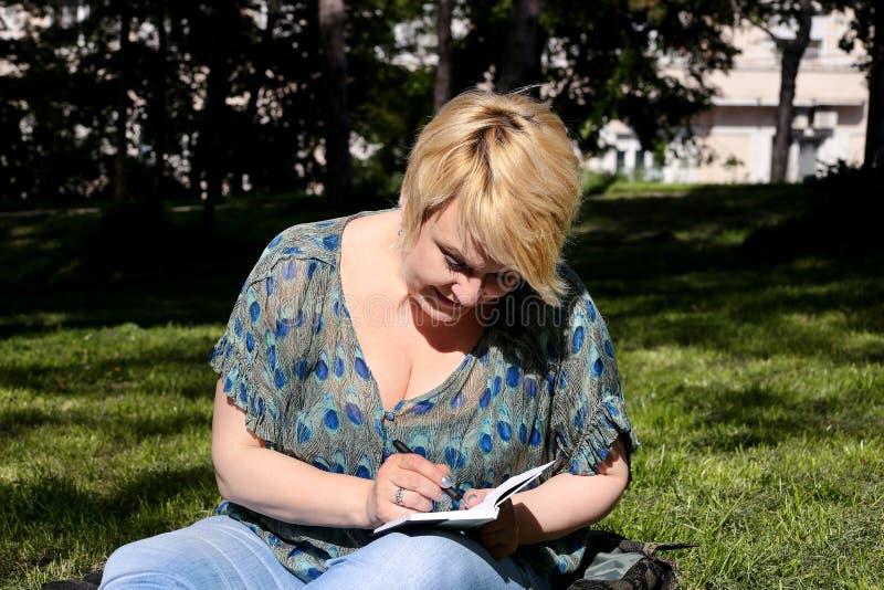 A mulher e o estudante que sentam-se na grama, tomam notas no caderno, aprendendo e escrevem pensamentos, escrevem o livro fotografia de stock