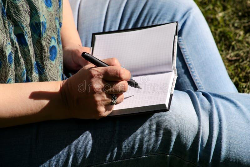 A mulher e o estudante que sentam-se na grama, tomam notas no caderno, aprendendo e escrevem pensamentos, escrevem o livro imagens de stock