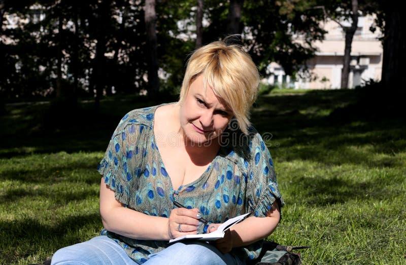 A mulher e o estudante que sentam-se na grama, tomam notas no caderno, aprendendo e escrevem pensamentos, escrevem o livro fotos de stock