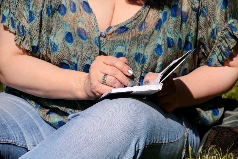 A mulher e o estudante que sentam-se na grama, tomam notas no caderno, aprendendo e escrevem pensamentos, escrevem o livro foto de stock