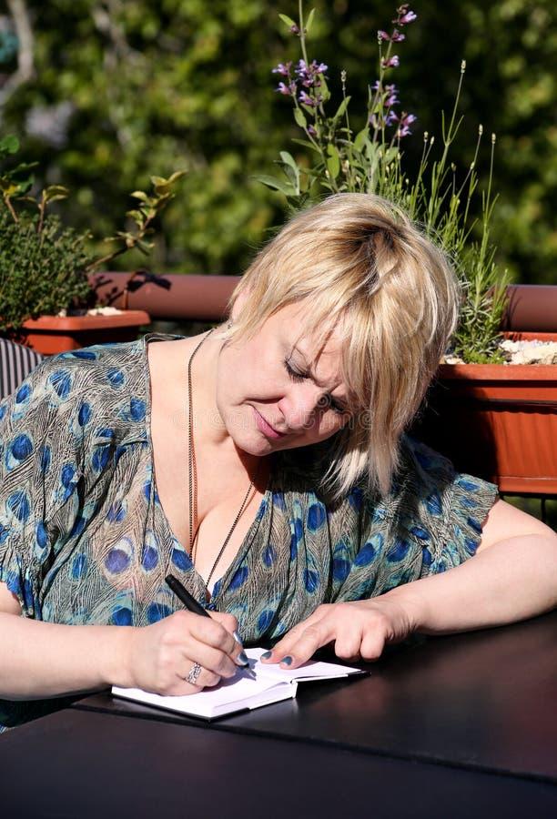 A mulher e o estudante que sentam-se na tabela na barra, tomam notas no caderno, aprendendo e escrevem pensamentos, escrevem o li imagens de stock