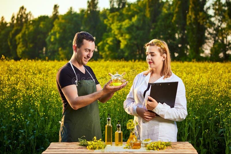 A mulher e o fazendeiro do agrônomo examinam o óleo de colza e o campo de florescência do canola da violação usando a tabuleta imagens de stock royalty free