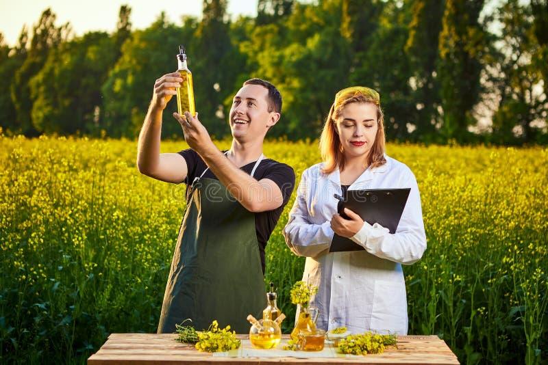 A mulher e o fazendeiro do agrônomo examinam o óleo de colza e o campo de florescência do canola da violação usando a tabuleta imagens de stock