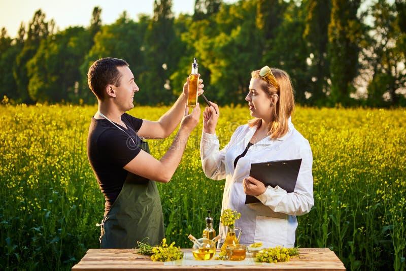 A mulher e o fazendeiro do agrônomo examinam o óleo de colza e o campo de florescência do canola da violação usando a tabuleta foto de stock
