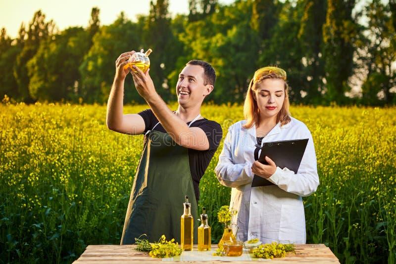 A mulher e o fazendeiro do agrônomo examinam o óleo de colza e o campo de florescência do canola da violação usando a tabuleta fotos de stock