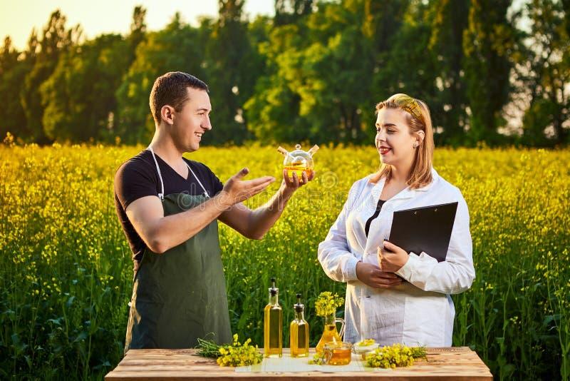 A mulher e o fazendeiro do agrônomo examinam o óleo de colza e o campo de florescência do canola da violação usando a tabuleta fotos de stock royalty free