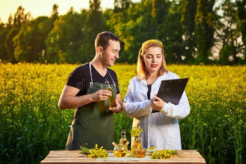 A mulher e o fazendeiro do agrônomo examinam o óleo de colza e o campo de florescência do canola da violação usando a tabuleta fotografia de stock royalty free