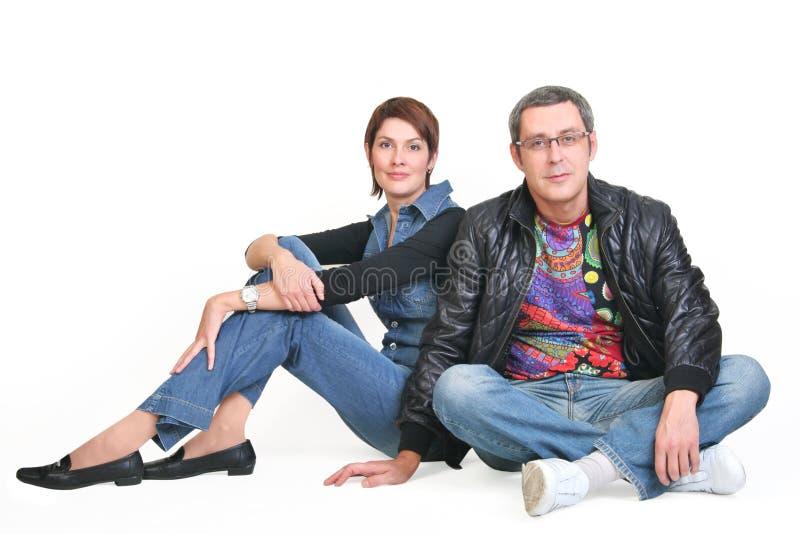A mulher e o homem, sentam-se junto fotos de stock