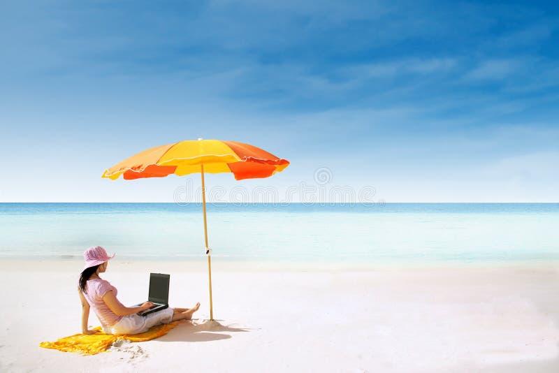 Mulher e portátil asiáticos na praia do paraíso fotografia de stock