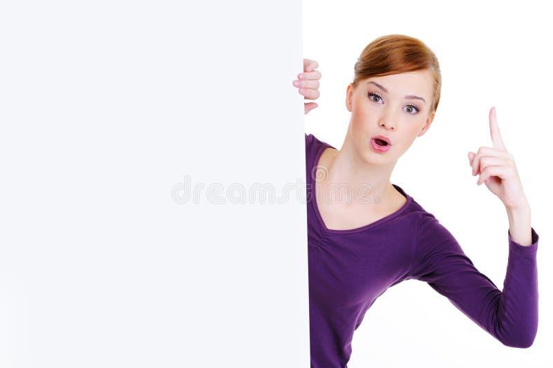 Mulher e quadro de avisos em branco com forefinger do elevador acima imagem de stock