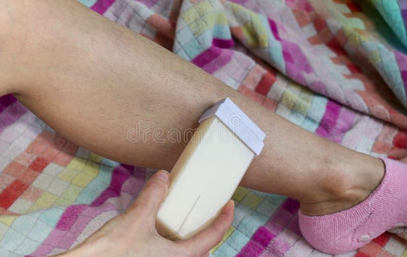 Mulher e seu pé peludo em uma toalha multi-colorida A menina realiza o procedimento da depilação pela cera foto de stock royalty free