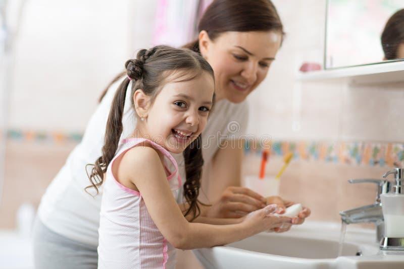 Mulher e sua filha garota lavando mãos com sabão no banheiro fotografia de stock royalty free