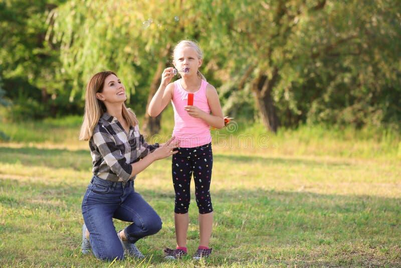 Mulher e suas bolhas de sabão de sopro da filha no parque fotografia de stock royalty free