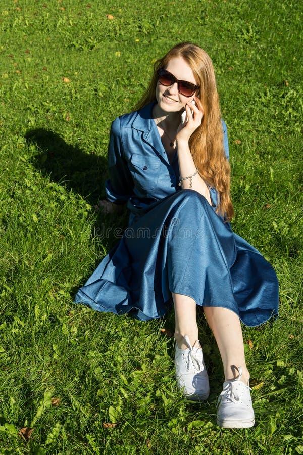 Mulher e telefone celular, gramado verde, verão Menina vermelha do cabelo, vestido azul, sentando-se na grama fora, guardando um  imagens de stock royalty free